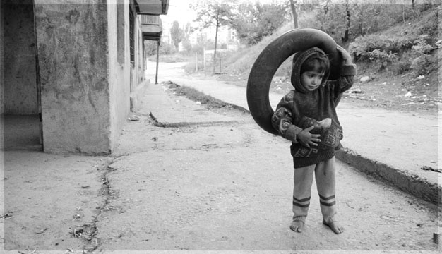 Boy uses old tire as a toy